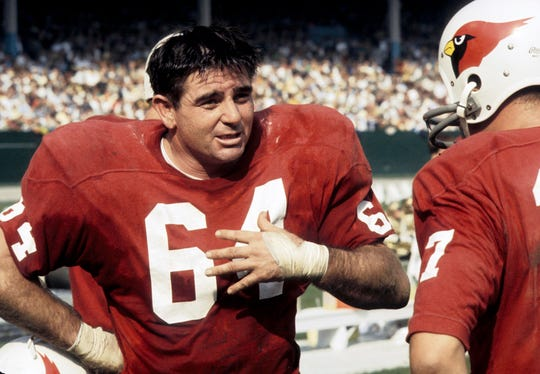 St. Louis Cardinals guard Ken Gray (64) talks to quarterback Jim Hart (17) during a game against the Browns on Oct 13, 1968 at at Cleveland Stadium.