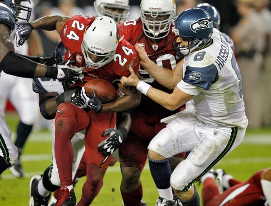 Adrian Wilson (24) is pulled down by Seahawks quarterback Matt Hasselbeck (8) after the Cardinals safety's interception during a game on Nov. 15, 2009.