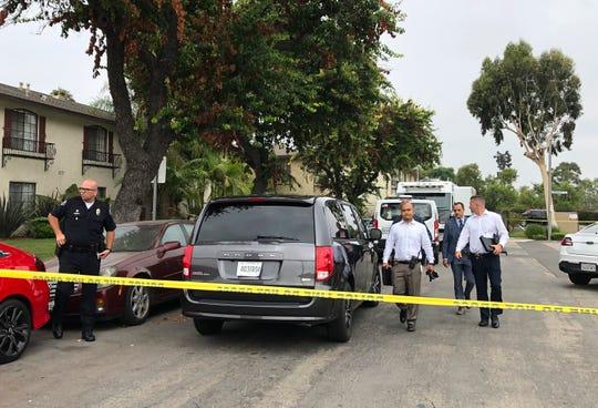 Policías de Garden Grove abandonan la escena de uno de los crímenes.
