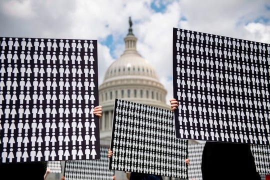 Manifestantes afuera del Capitolio muestran un cartel con 11,400 siluetas, que representan los muertos con armas de fuego que ha habido desde que el gobierno aprobó la actual ley de armas.