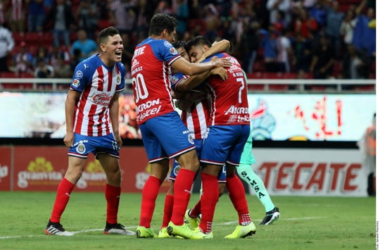 Jugadores de Chivas celebran uno de sus goles.