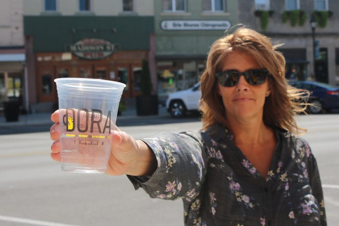 """Nikki Adams, president of Main Street Port Clinton, shows a sample DORA cup used in Toledo earlier this year. Now Port Clinton has its own cup for """"MORA."""""""
