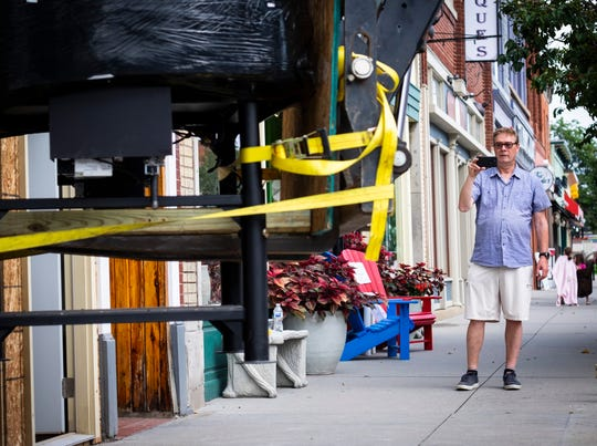 John Marion, co-owner of BellaBolla pizzeria, takes a video on his cell phone as the store's pizza oven is lifted through the front of the building Thursday, Aug. 8, 2019, in downtown Port Huron.