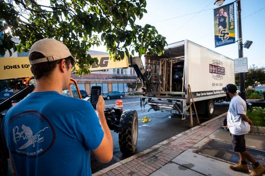 Luke Marion, co-owner of BellaBolla, takes a video on his cell phone as the store's pizza oven is lifted out of the back of a moving truck Thursday, Aug. 8, 2019, in downtown Port Huron.