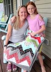 From left, Amie Fredericks and her daughter Alyssa sit on the front porch of their Clinton Corner home with the dog quilt that  Alyssa made Aug 7, 2019. Alyssa and her brother Kyle will be entering the Needlework and Stitchery competition at the Dutchess County Fair.