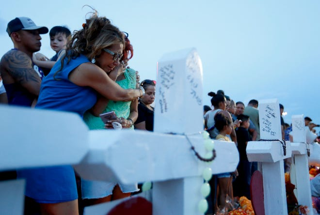 Rebecca Najera, left, hugs Elsa Escobar as they joined others gathered Monday, Aug. 5, 2019 in front of crosses representing the victims who died in the shooting at a Walmart in El Paso, Texas.  (Vernon Bryant/The Dallas Morning News/TNS)