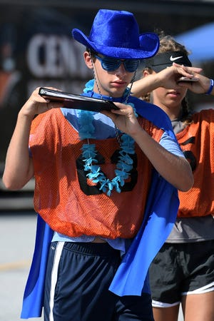 """Central York High School junior Ryan McCabe wears a costume during a Panther Marching Band practice at the school Thursday, Aug. 8, 2019. Band members participated in a """"color war"""" during the session, with class members wearing the grade's designated color. Prizes were awarded for costume creativity. Band members were completing the week's main band camp schedule which is comprised of daily 10-hour sessions. They practice without instruments while learning the show's choreography. The first football game is Aug. 23 at West York. Bill Kalina photo"""