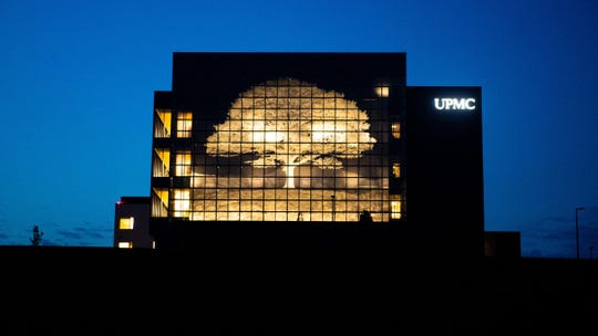 The picturesque illuminated tree on the side of the UPMC Pinnacle Memorial Hospital shines in the night, August 7, 2019.