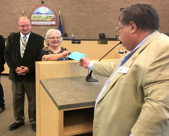 Mayor Roy Edgington presents outgoing council woman Sue Siedl with a card and a key to the city as council member Ray Lacy looks on.