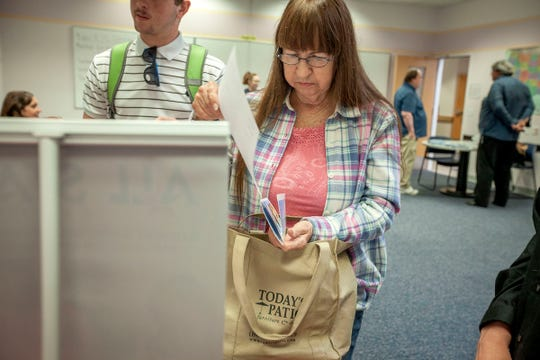 Diana Ruiz, 69, of Sweet Home, puts some paperwork in her bag as she visits with perspective employers during a Salem Goodwill Job Connection job fair focusing on job seekers who are 50 and older. The Salem fair was on of four held around the state August 7, 2019 to let job seekers  meet face-to-face with employers who are ready to hire.