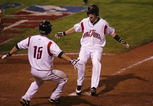 Salem-Keizer's Dan Cook (right) gets ready to jump into the arms of teammate Ryan Cavan after he scored the winning run in the bottom of the 13th inning to defeat Tri-City 2-1 to win the Northwest League Championship at Volcanoes Stadium on Thursday, Sept. 10, 2009.