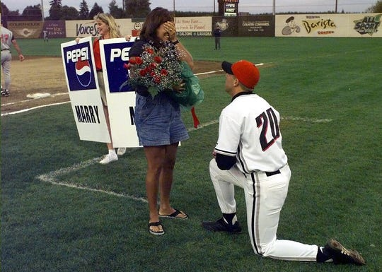 Krissy Hersey can't believe what's happening as Volcanoes pitcher Mike Huller proposes to her in the middle of the third inning.