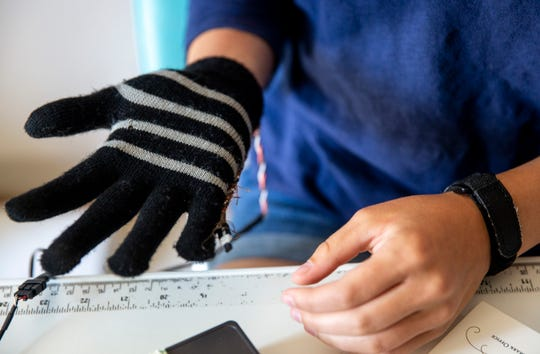 "Allie Weber, 14, wears her ""Frost Stopper"" gloves she designed as a fifth-grader for the Spark Lab Global Invent-It Challenge. Weber's gloves are temperature sensing and have a built in frost bite warning system."