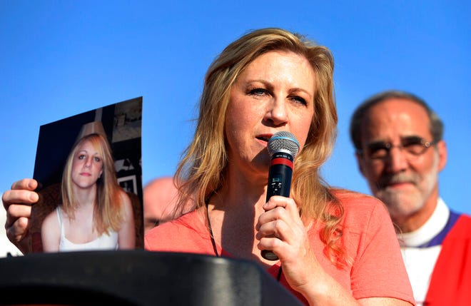 FILE - In this June 28, 2015, file photo, Carolyn Tuft, holds a photo of her 15-year-old daughter Kirsten, who was killed in the 2007 Trolley Square shooting, during a march and rally to urge people of faith to seek common ground to curtail gun violence, in Salt Lake City.  Tuft, survived a mass shooting in Salt Lake City 12 years ago is slowly dying from lead poisoning after a shotgun left 300 pellets in her body, a report said. Tuft, 56, has struggled with grief after surviving the 2007 Trolley Square mall shooting that killed her 15-year-old daughter, KUTV-TV reported Tuesday, Aug. 6, 2019. (Scott Sommerdorf/The Salt Lake Tribune via AP, File) ./The Salt Lake Tribune via AP)