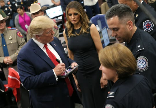 President Donald Trump signs autographs for first responders Wednesday, Aug. 7, 2019, at the Office of Emergency Management in El Paso, Texas. Trump met with first responders who were at the scene of the mass shooting at Walmart that killed 22 and wounded 25.