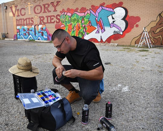Artist Gabriel Corona selects a spray nozzle tip as he works on a large mural at Victory Ministries Church on Monroe.
