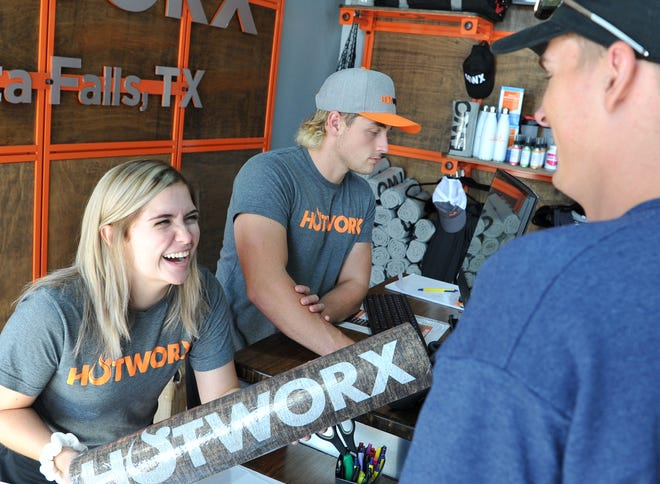 HOTWORX (Wichita Falls, TX - Call Field) trainers/sales associates Elise Miller, left, and Gavin Clark, right, help a customer Thursday at the newly opened 24-hour fitness studio located on Call Field Road, inside the Burlington Coat Factory shopping center.