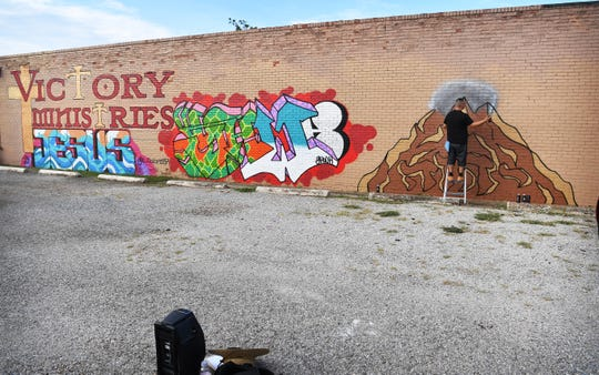 A large mural at Victory Ministries Church on Monroe is nearing completion as artist Gabriel Corona puts on the finishing touches.
