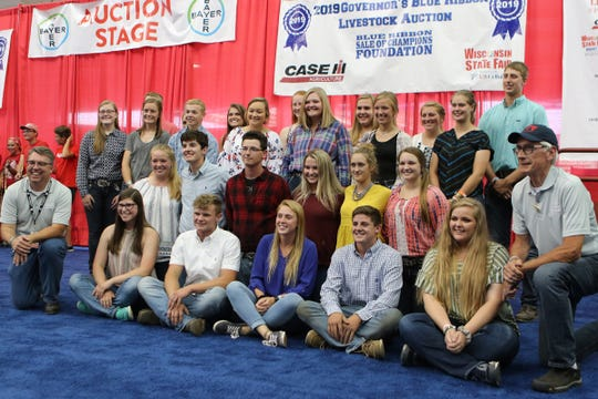 Governor's Blue Ribbon scholarship recipients pose for a photo with DATCP Secretary Brad Pfaff (left) and Governor Tony Evers (right) at the Governor's Blue Ribbon Auction on Aug. 7 at the Wisconsin State Fair.