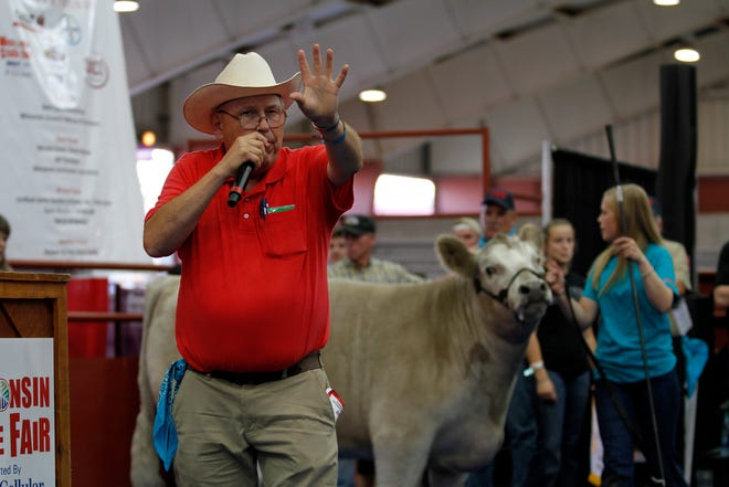 FILE - In this 2019 photo, Auctioneer Gary Finley auctions the reserve grand champion steer owned by Lauren May of Mineral Point during the Governor's Blue Ribbon Livestock Auction at the Wisconsin State Fair on Aug. 7. The crossbred steer sold for $22,500.