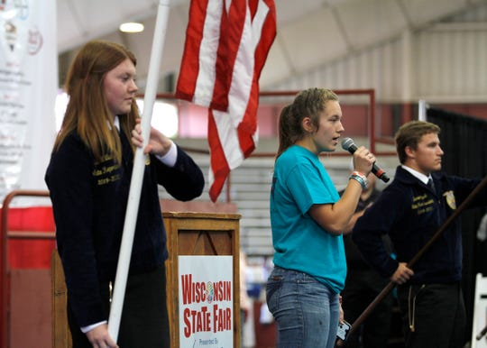 Trenna Cherney, of Wonewoc, sings the National Anthem as the Wisconsin State FFA color guard presents the flags at the Governor's Blue Ribbon Livestock Auction on Aug. 7.