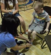 Julian McCoy, of Zanesville, tries on a pair of shoes with the help of Angie Fuller, from Muskingum County Children Services, during Thursday's Lace Up for Kids at the Zanesville Civic League Community Center. This was the 32nd year for the event, which is organized by Eastside Community Ministries.
