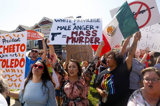 People protest near Miami Valley Hospital in Dayton, Ohio, on Aug. 7, 2019, before President Donald Trump's visit to victims being treated at the hospital.