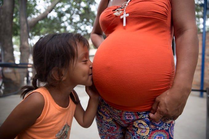 Venezuelan migrant Fabiana Correa Martinez, 4, kisses the belly of her pregnant mother Nairobi Correa Martinez in a migrant soup kitchen in Cucuta, Colombia on Feb. 9, 2019.