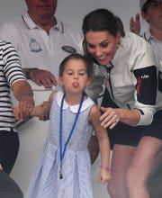 Princess Charlotte sticks her tongue out to the crowd as her mother, Duchess Kate of Cambridge, laughs during the King's Cup sailing regatta off the Isle of White, Aug. 8, 2019.
