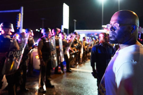 A demonstrator in front of police officers during a protest in Ferguson, Missouri, on Aug. 9, 2015.