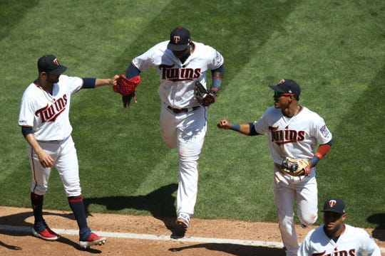 Aug 7: Minnesota Twins starting pitcher Martin Perez (33) celebrates with third baseman Miguel Sano (22) and shortstop Jorge Polanco (11) after completing a triple play during the third inning against the Atlanta Braves at Target Field.
