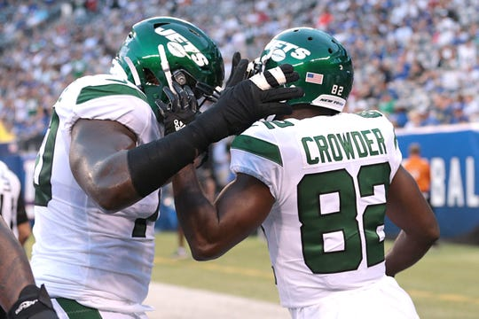 New York Jets wide receiver Jamison Crowder (82) celebrates after a touchdown reception with offensive guard Kelechi Osemele (70) during the first half against the New York Giants at MetLife Stadium.