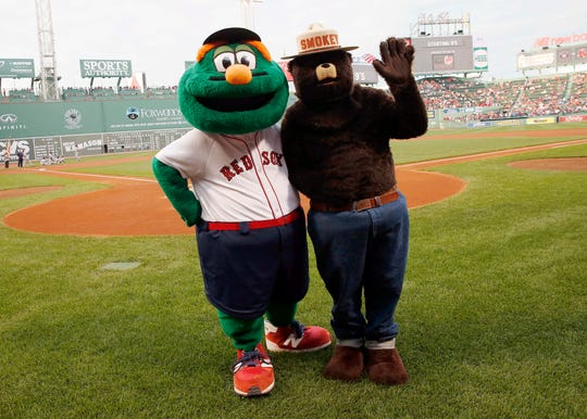 Smokey Bear poses with the Boston Red Sox mascot Wally before a baseball game between the Red Sox and the Houston Astros in Boston on Aug. 15, 2014.