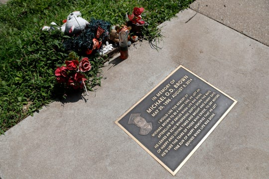 In this July 25, 2019, photo, flowers and other items lay near a memorial plaque in the sidewalk near the spot where Michael Brown was shot and killed by a police officer five years ago in Ferguson, Mo.