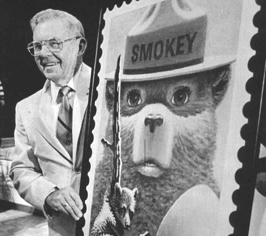 Ray Bell stands next to an oversized copy of the Smokey Bear stamp on August 13, 1984. Bell cared for Smokey Bear after the young cub was rescued from a forest fire in 1950.