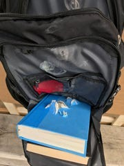 Hardcover books, placed inside a bulletproof backpack but outside the pack's protective Kevlar shell, torn to shreds by ammunition of different caliber.
