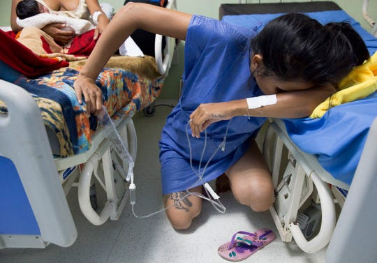 Venezuelan migrant Yulianis Rodriguez hunches down in Colombia's Hospital San Jose as she struggles to cope with the pain of labor without an epidural May 5.