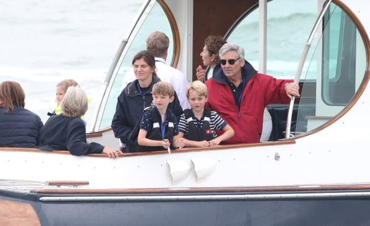 Prince George and his maternal grandfather, Michael Middleton, watch the inaugural Kings Cup regatta hosted by George's parents, Prince William and Duchess Kate of Cambridge, on Aug 8, 2019, off the Isle of Wight.