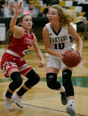 Brooke Ellestad, right, of Oshkosh North drives to the basket against Kate Karch of Kimberly during a game last season in Oshkosh.