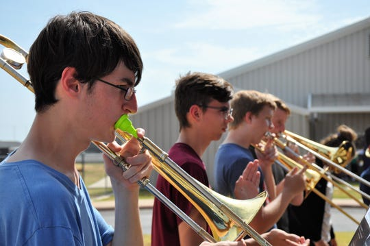 Zachary Tellez, left, and other members of the Wylie High School band trombone section rehearse during marching band camp on Friday.