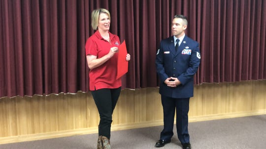 State Sen. Dawn Buckingham, left, presents Tech Sgt. Justin Dillinger with a proclamation Friday, recognizing the Dyess Air Force Base officer for saving a boy drowning in a pool at Dillinger's apartment complex last month.