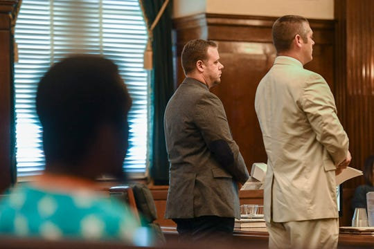 Ex-officer Chris Hickman, center, stands with his attorney, Thomas Amburgey, during his plea hearing August 9, 2019. Johnnie Rush, the victim of the 2017 beating, is in the foreground.