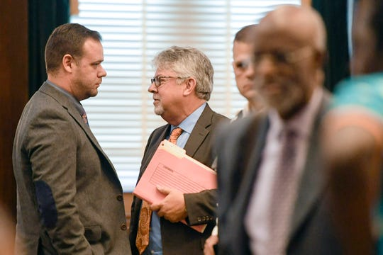 Ex-Asheville police officer Chris Hickman, left, talks to Campbell University law professor Jon Powell after his Aug. 9, 2019, plea. James Ferguson, attorney for Johnnie Rush, the man Hickman acknowledged to beating, is seen in the right foreground.