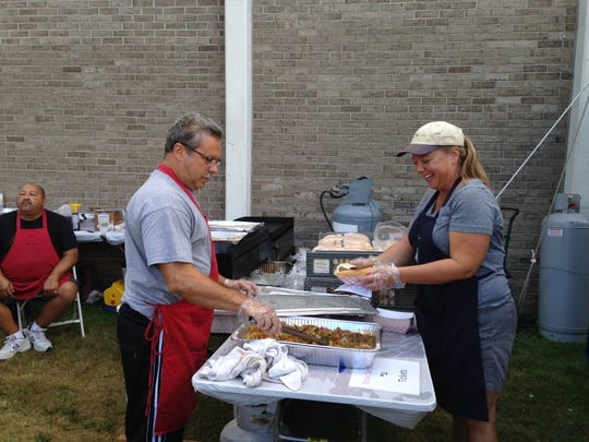 Mark Cerra, left, and Colleen O?Neill help in the food tents at the 2014 St. Mary of the Assumption bazaar in Binghamton.