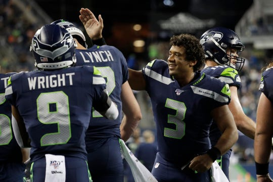 Seattle Seahawks quarterback Russell Wilson (3) greets backup quarterback Paxton Lynch, second from left, after Lynch scored a touchdown against the Denver Broncos during the second half of an NFL football preseason game Thursday, Aug. 8, 2019, in Seattle.
