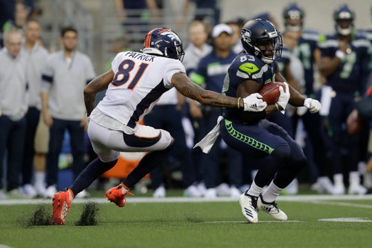 Denver Broncos' Tim Patrick tackles wide receiver David Moore on a kick return during the first half of an NFL football preseason game, Thursday, Aug. 8, 2019, in Seattle.