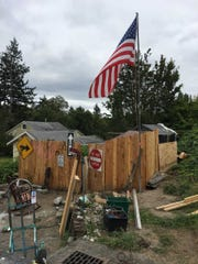 As the county took a property owner to court to establish who was responsible for an East Bremerton encampment, the man who lives there made several improvements, including installing a flag pole.