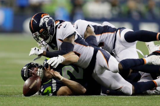 Seattle Seahawks quarterback Paxton Lynch, lower left, loses the ball as he falls under Denver Broncos cornerback DeVante Bausby (41) during the second half of an NFL football preseason game, Thursday, Aug. 8, 2019, in Seattle. (