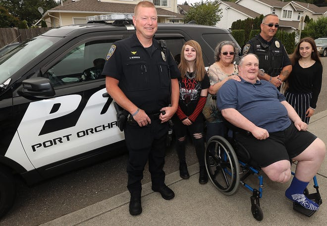 Port Orchard Police Officer Steve Morrison, Isabel Davis, 13, Mary O'Connor, Clancy O'Connor, Port Orchard Police Officer Bill Schaibly and Hannah Davis, 16, pose for a portrait in the O'Connor's driveway of their Port Orchard home. The officers struck upon the Davis' garage sale to raise money for new school clothes and collected donations for their cause.