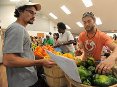 Adam Kelly, right, the food sourcing and volunteer coordinator for Bounty & Soul,  works with a volunteer during the Aug. 6 market at St. James Episcopal Church.
